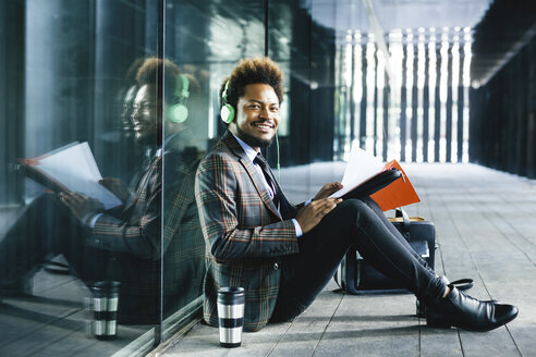 Smiling young businessman with headphones and folder sitting outdoors - EBSF001123