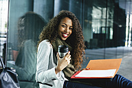 Smiling young businesswoman with coffee to go mug and folder sitting outdoors - EBSF001129