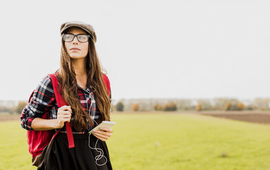 Young woman with backpack and portable device in the countryside - UUF006037