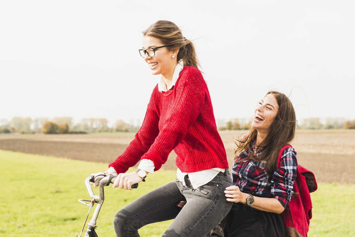 Two happy young women sharing a bicycle in rural landscape - UUF006040 - Uwe Umstätter/Westend61