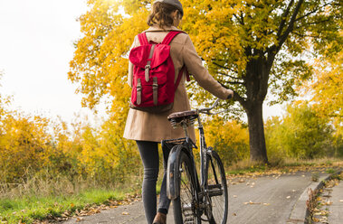 Young woman with backpack pushing her bicycle in autumn landscape - UUF006046