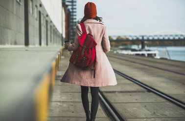 Young woman with backpack walking at the riverside - UUF006088