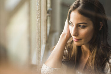Brunette woman looking out of window - UUF006094