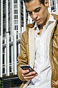 Young man with a leather jacket using his cell phone - ABZF000153