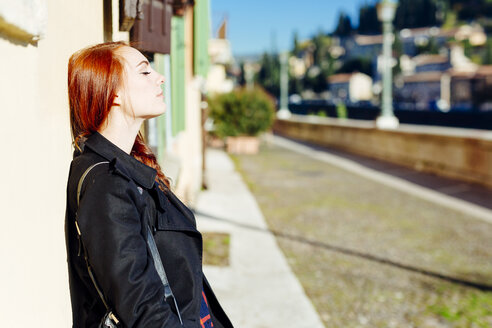 Italy, Verona, young woman leaning against house wall in sunlight - GIOF000530