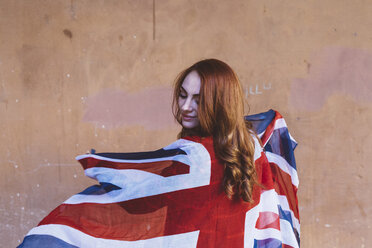 Smiling woman holding a British flag - GIOF000533