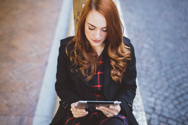 Young woman looking at digital tablet outdoors - GIOF000536