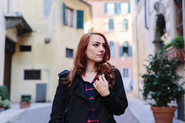 Italy, Verona, young woman in the city looking around - GIOF000539
