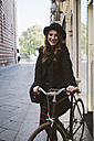 Italy, Verona, happy young woman with bike in the city - GIOF000545