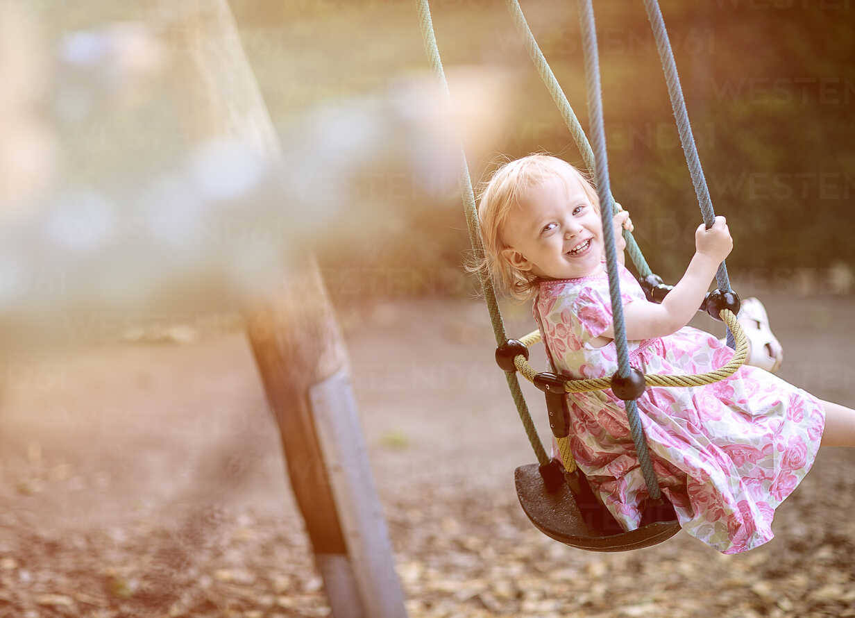 Portrait of blond little girl wearing dress with floral design sitting on a swing - NIF000051 - Nailia Schwarz/Westend61