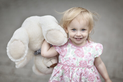 Portrait of smiling blond little girl with her teddy bear - NIF000054