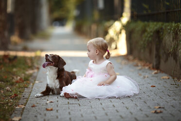 Blond little girl wearing tulle dress sitting besides her dog on pavement - NIF000060