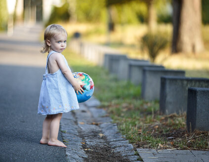 Barefoot blond little girl standing with her ball at roadside - NIF000063