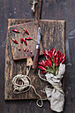 Bunch of red chili peppers, cord and knife on wooden boards - SBDF002409