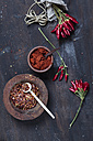 Bunches of red chili peppers, cord plate of chili flakes and bowl with chili powder on wood - SBDF002412
