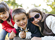 Three laughing children in a park - MGOF001059