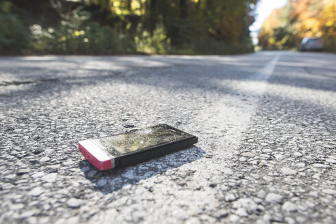 Broken smartphone lying on the road - DEGF000584