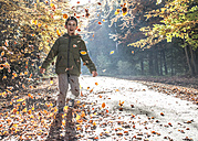 Boy playing with leaves in autumnal forest - DEGF000587