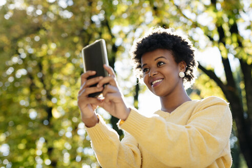 Beautiful black woman with smartphone, outdoor in autumn - MAUF000006
