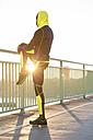 Athlete stretching on bridge railing - MADF000610