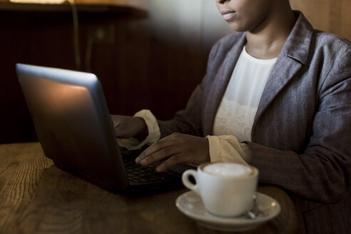 Young woman sitting in a cafe working with laptop - MAUF000018