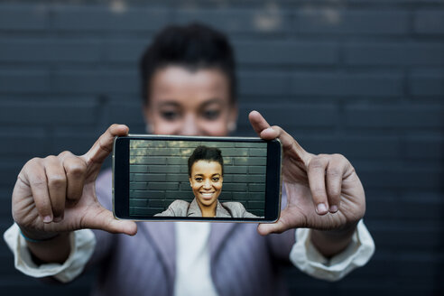 Photography of young woman taking a selfie on display of smartphone - MAUF000036
