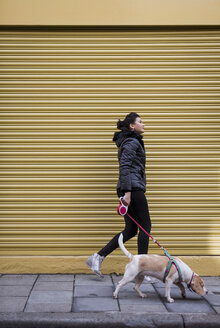 Woman and her dog walking on pavement in front of a roller shutter - MAUF000040