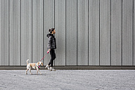 Woman and her dog walking on pavement in front of a metal facade - MAUF000052