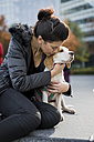 UK, London, woman cuddling her dog - MAUF000055