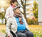 Senior woman with husband in wheelchair outdoors - UUF006126