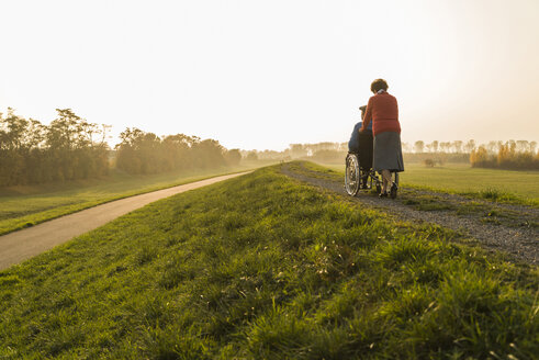 Senior woman pushing husband in wheelchair in the nature - UUF006144