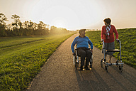 Smiling senior couple with wheelchair and wheeled walker on a path - UUF006156