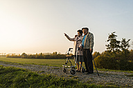Senior couple with walking stick and wheeled walker standing in the nature - UUF006159