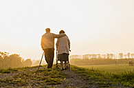 Senior couple walking with walking stick and wheeled walker in the nature - UUF006162
