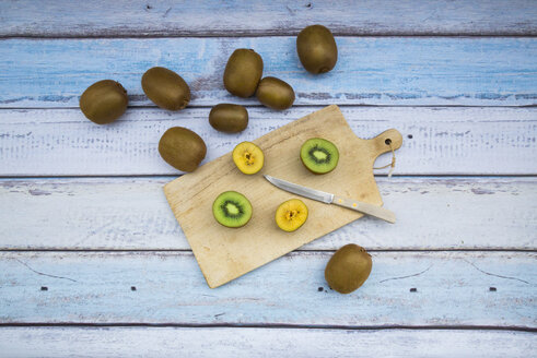 Green and golden kiwis on chopping board, wood - LVF004178