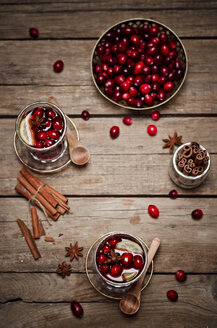 Glasses of cranberry juice with fresh cranberries, lemon slices and spices on wood - CZF000232
