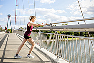 Germany, Frankfurt, young athlete stretching on bridge - PUF000436