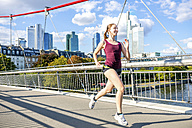 Germany, Frankfurt, young woman jogging on bridge - PUF000439