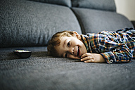 Portrait of smiling little boy lying on the couch besides remote control - JRFF000198