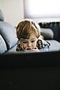 Portrait of little boy lying on the couch looking at digital tablet - JRFF000204