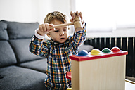 Little boy playing with wooden motor skill toy - JRFF000207