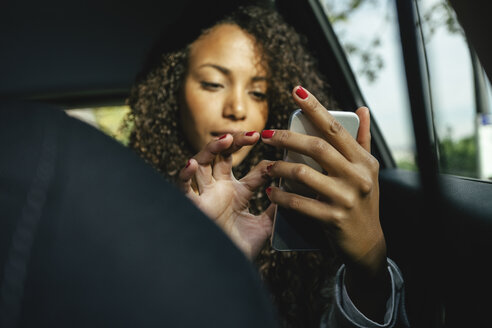 Young woman sitting on back seat of a car using smartphone - EBSF001136