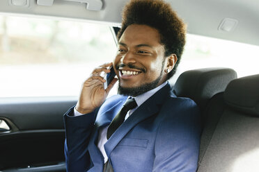 Smiling businessman sitting on back seat of a car telephoning with smartphone - EBSF001139