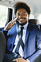 Portrait of smiling businessman sitting on back seat of a car telephoning with smartphone - EBSF001142