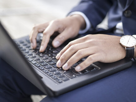 Germany, Cologne, Young businessman typing on laptop, close up - MADF000691