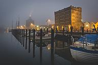 Germany, Eckernfoerde, harbor with old warehouse in fog - KEBF000281
