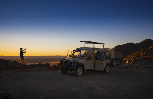 Africa, Namibia, Namib Desert, Landrover and female tourist in Kulala Wilderness Reserve - AMF004442