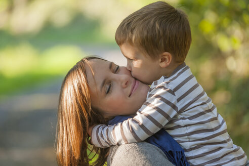 Little boy hugging and kissing his happy mother - PAF001477
