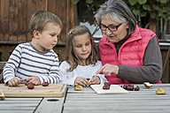 Two children and their grandmother tinkering with chestnuts - PAF001486