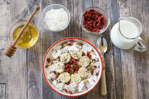 Bowl of muesli with banana slices, chia seeds, coconut chips and goji berries - SARF002327